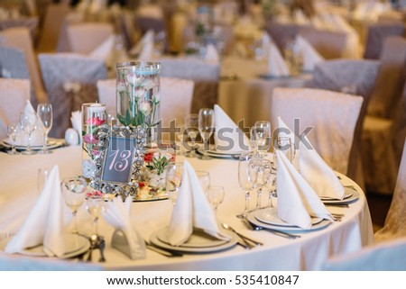 Frame with number 13 stands on mirror tray with flowers in the middle of dinner table