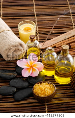 frangipani with stones ,candle, oil ,soap on mat background