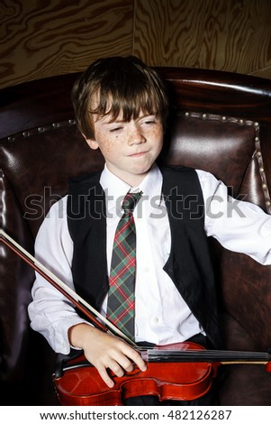 Freckled red-hair boy with violin sitting in the arm-chair. Studio shooting.
