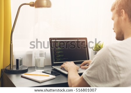 freelance programmer working from home. php website code on screen. Visible translations for page titles - Production, Project management, Partners and Contacts in Latvian and Russian languages