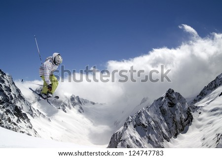 Freestyle ski jumper with crossed skis against blue sky and snow mountains
