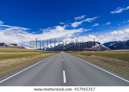 freeway receding to the horizon under a blue sky among the high snow-capped mountains