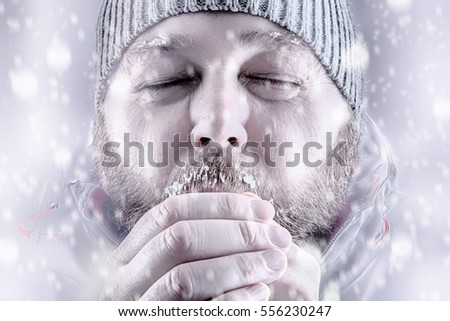 Freezing cold man in snow storm white out trying to keep warm by blowing into his hands. Wearing a beanie hat with eyes closed and winter coat. Frost and ice on his beard and eyebrows.