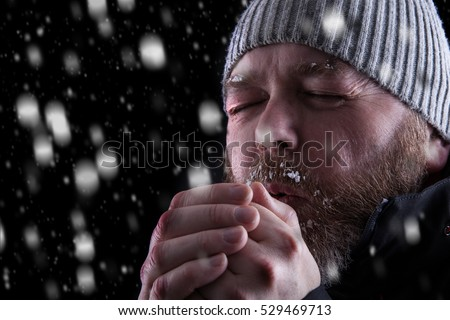 Freezing cold man standing in a snow storm blizzard trying to keep warm. Eyes closed and blowing warm air into his hands. Wearing a hat and coat with frost and ice on his beard and eyebrows.