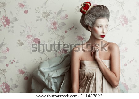 French kitsch, grotesque concept. Portrait of beautiful luxurious girl wearing crown in Marie Antoinette style. Perfect make-up and hairdo. Studio shot