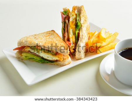fresh and delicious classic club sandwich and cup of coffee and vegetable