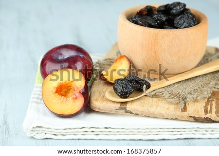 Fresh and dried plums in wooden bowl on napkin, on wooden background