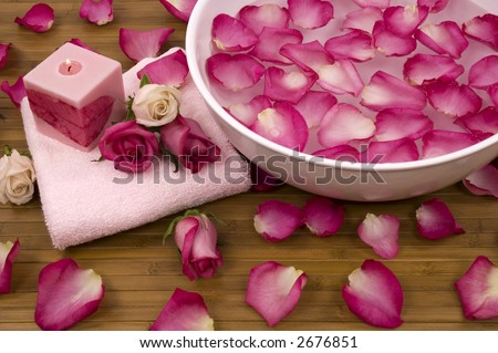 Fresh bright pink roses, petals, candle, and towel in a spa