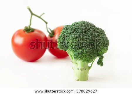 fresh broccoli and tomatoes isolated on white background