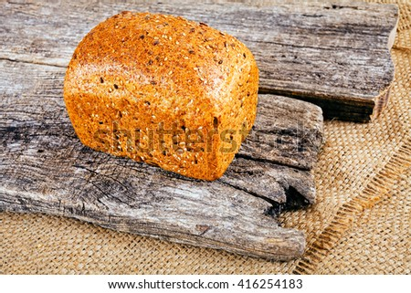 Fresh brown bread on old wooden background