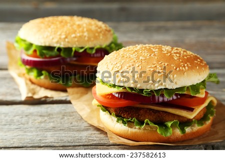 Fresh burgers on grey wooden background