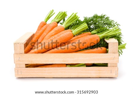 Fresh carrot roots (Daucus carota ssp. sativus) in wooden crate on white