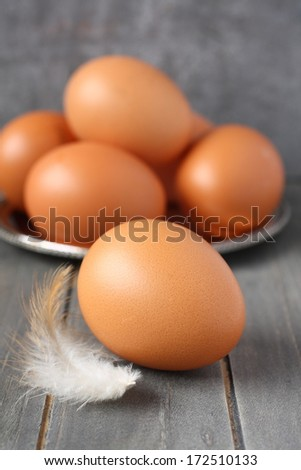 Fresh chicken eggs and feather on rustic wooden background