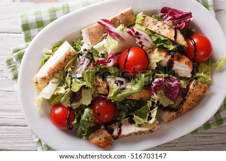 Fresh chicken salad, tomatoes and herbs with balsamic sauce close-up ...