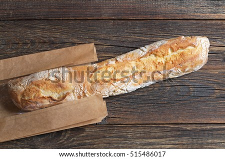 Fresh ciabatta bread on dark wooden table with paper package, top view