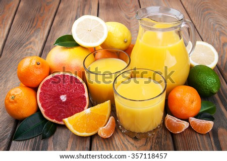 Fresh citrus juice with fruits on a wooden table