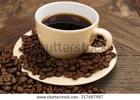 Fresh cup of coffee  with roasted coffeebeans around. Old wooden table as background.