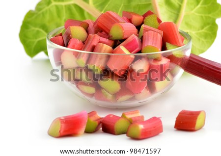 Fresh cut up rhubarb in glass dish with stalk and leaf behind