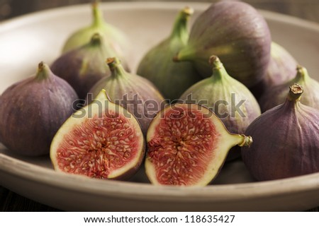 Fresh figs in a bowl with sliced fig in the front.