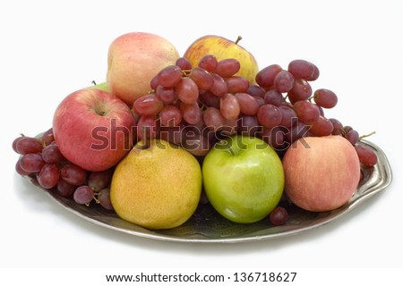 Fresh fruit on the large plate on a white background.