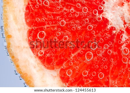 Fresh grapefruit in water with bubbles