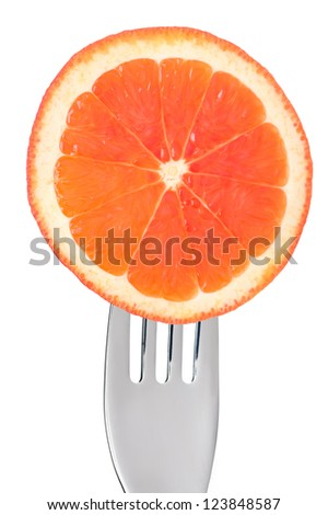 fresh grapefruit slice on a fork isolated against white background