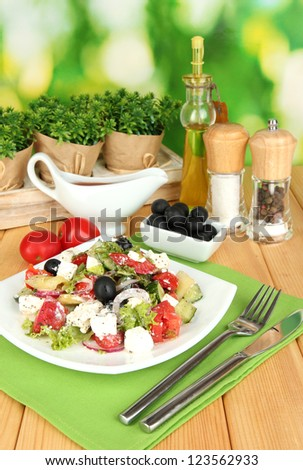 Fresh greek salad on plate on wooden table on natural background