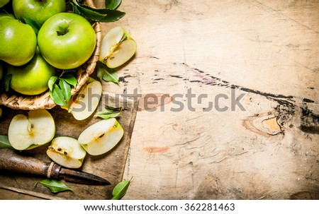 Fresh green apples in the basket with knife . On a wooden table. Free space for text . Top view