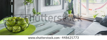 Fresh green apples on table in bright living room, panorama