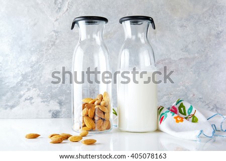fresh homemade almond milk in a transparent bottle and almonds. vegetarian alternative to milk.
