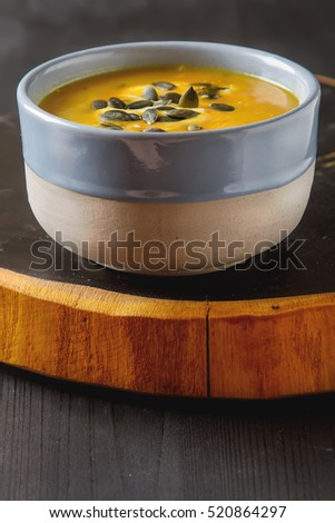 Fresh homemade carrot soup with pumpkin seeds and sour cream in a blue vintage plate.