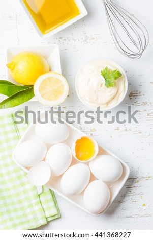 Fresh homemade white sauce Mayonnaise and ingredients eggs, lemon olive oil on white background. Top view