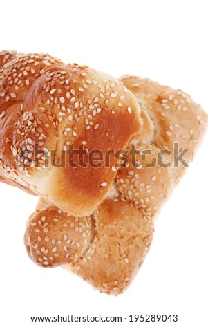 fresh loaf of light wheat bread topped by sesame seeds isolated over white background
