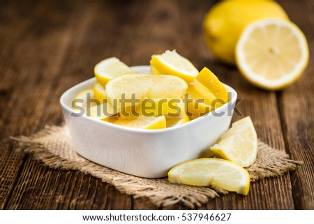 Fresh made Lemon (sliced) on an old and rustic wooden table (selective focus, close-up shot)