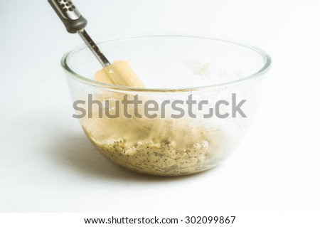 Fresh mixed lemon and poppy seed biscuit dough in glass mixing bowl with spatula; seamless white background.