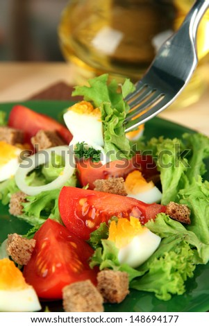 Fresh mixed salad with eggs, tomato, salad leaves and other vegetables on color plate, on bright background