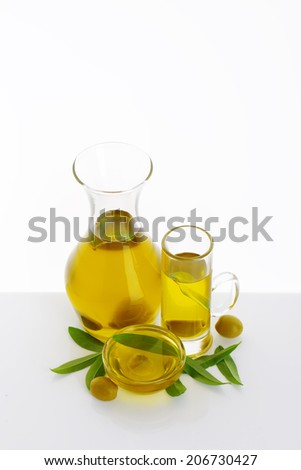 fresh olive oil in various glass, olives and olive leaves on white background