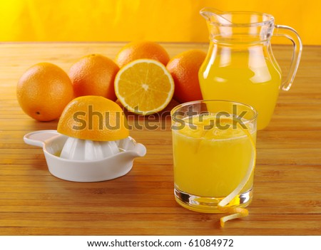 Fresh orange juice with orange juice squeezer, oranges and a jar of orange juice on wooden mat with orange background (Selective Focus)