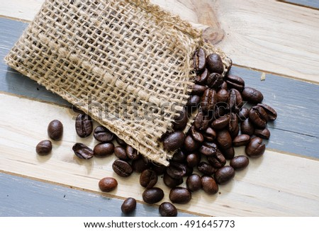 Fresh Organic and Arabica coffee beans spill out of a small burlap bag
