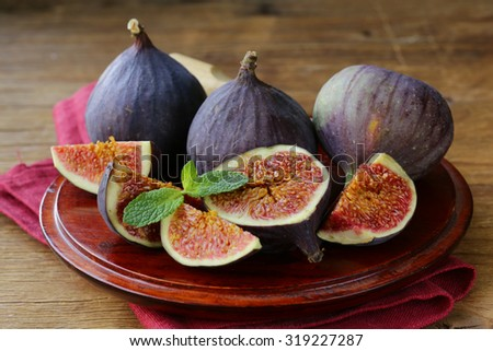 fresh organic purple fig fruit on wooden plate