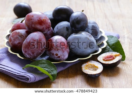 fresh organic purple plums on a wooden table