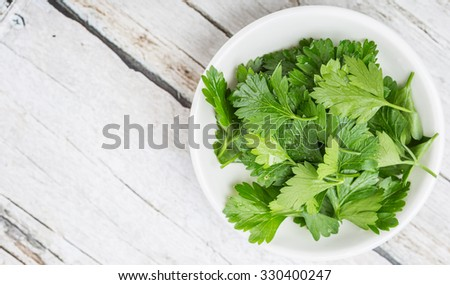 Fresh parsley leaves in white bowl over wooden background