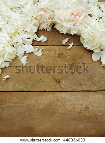 Fresh peony petals on wooden background