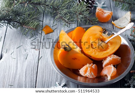 fresh persimmon fruit and mandarin on wooden table with Christmas ...