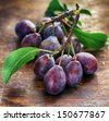 fresh plums on wooden table - stock photo