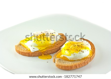 Fresh poached eggs on rye toast with a white background.