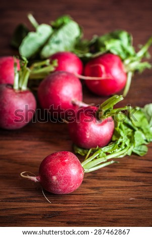 Fresh radishes on a wooden cutting board.