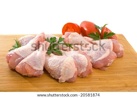 Fresh raw chicken wings on chopping board with roma tomatoes