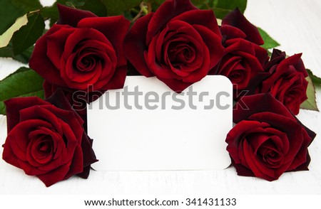 Fresh Red roses and greeting card on a wooden background