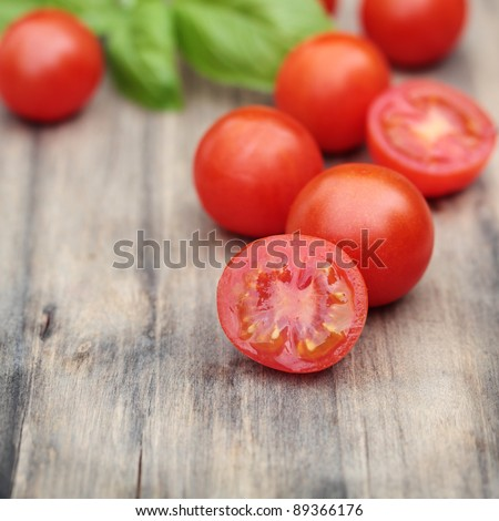 Fresh, ripe cherry tomatoes on an old chopping board. Basil leaves in the background.